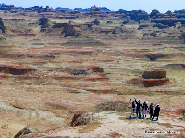 A group of people dwarfed by the Ghost City Rock Formations