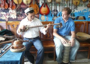 A Uyghur man teaching Josh to play a Uyghur instrument