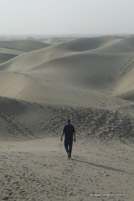 A small figure walks through endless Taklamakan desert sands