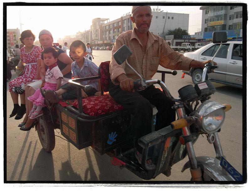 A family rides a motorcycle taxi in Kuqa, Xinjiang