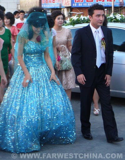 A Uyghur bride and groom walk to their wedding