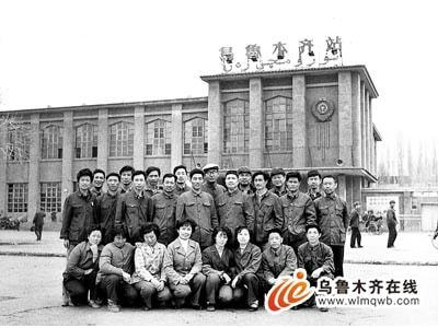 Men pose in front of the 1982 Urumqi Train Station