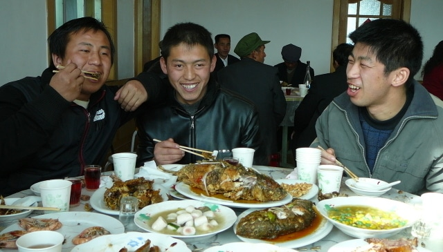 Three men eating at a banquet full of mostly healthy Chinese food