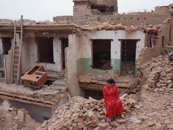 A woman sits on the rubble of her Old City home in Kashgar, Xinjiang