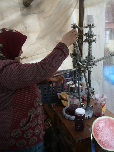 A vendor squeezes pomegranate juice in Xinjiang