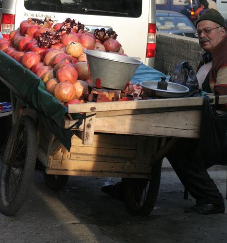 A man sells pomegranates off a street cart