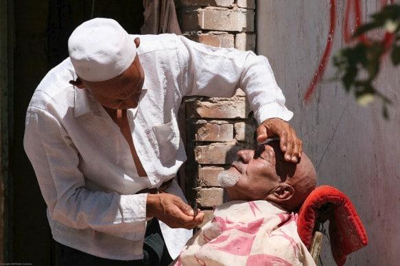 A Uyghur man getting shaved in Kashgar, Xinjiang (China)