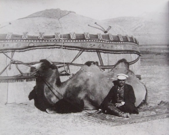 Sven Hedin sits with his camel outside a Xinjiang yurt