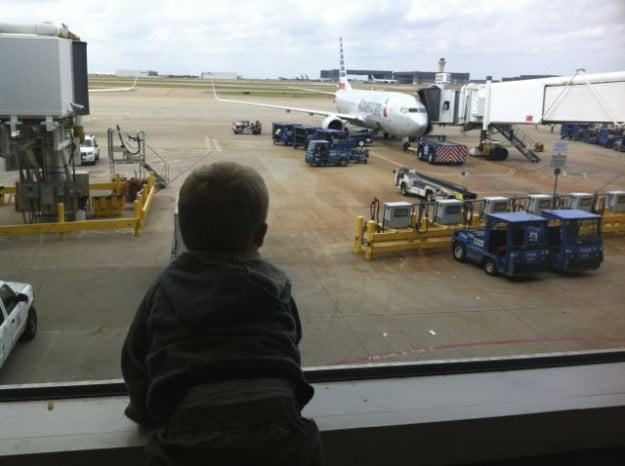 A young boy waits for his flight in an airport