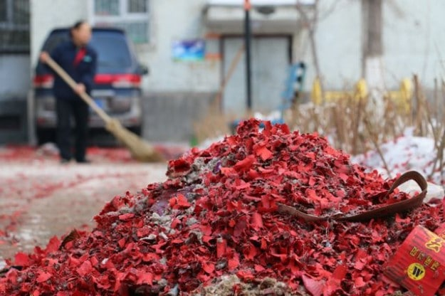 A worker cleans up the mess left behind from Chinese New Year celebrations