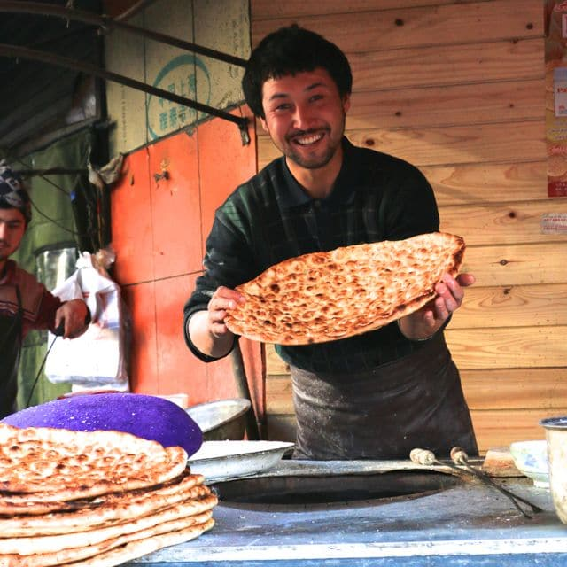 A Uyghur bread man in Xinjiang, China is all smiles