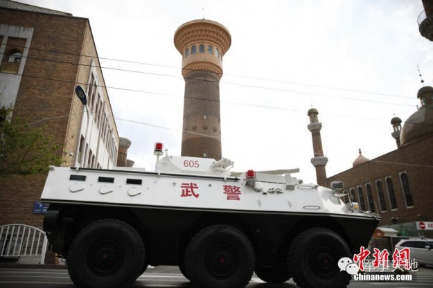 A Chinese tank rolls past the Urumqi International Bazaar in Xinjiang on May 24th, 2014