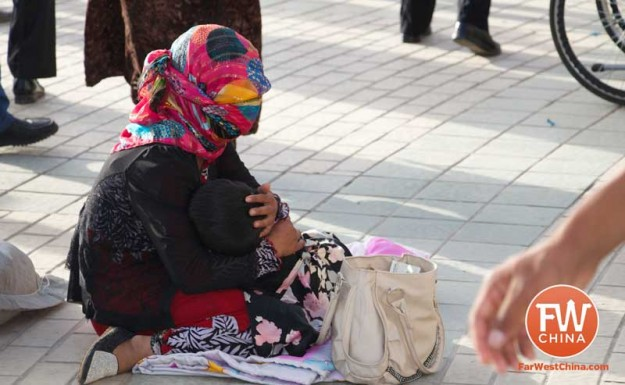 A beggar pleads for charity in front of the Id Kah Mosque in Kashgar, Xinjiang in China