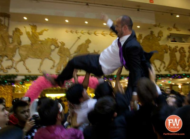 Uyghur groom gets tossed in the air by his men during a Uyghur wedding in Urumqi, Xinjiang