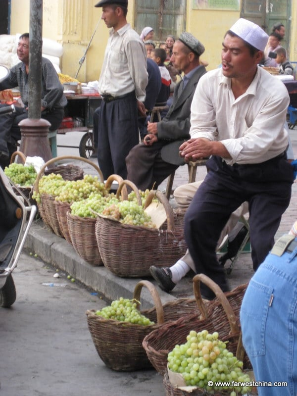 A Uyghur man sells grapes in Kashgar, Xinjiang