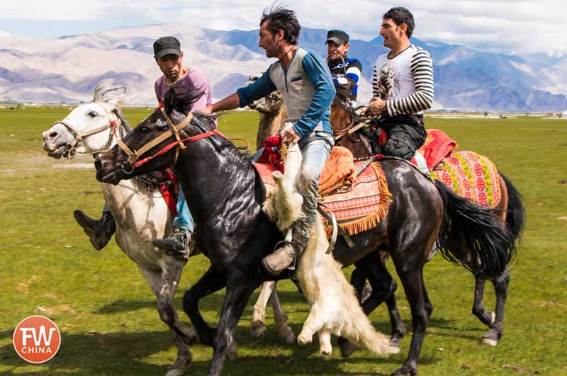 "Buzkashi riders carry the goat carcass ""ball"""