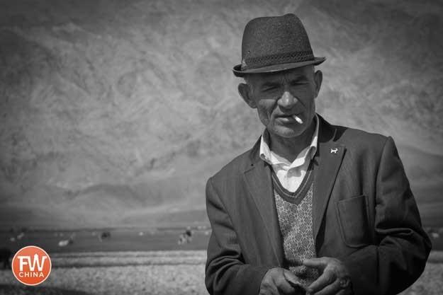 A Tajik man smoking on the grasslands in Tashkorgan, Xinjiang
