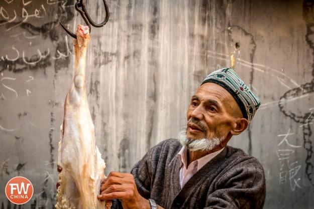 A Uyghur man cuts a sheep carcass in Urumqi, Xinjiang