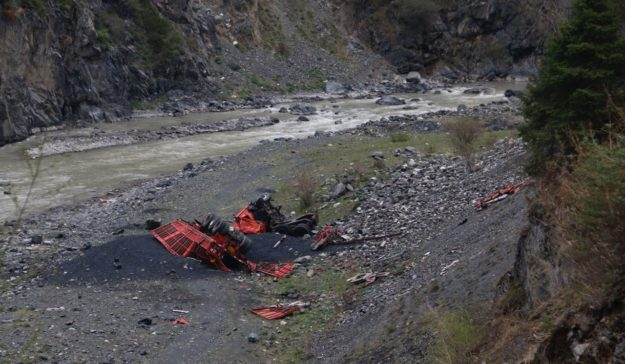 A crashed truck sits at the bottom of the valley