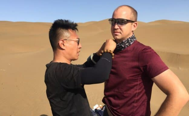 Getting mic'ed up by CCTV crew at the Shanshan sand dunes